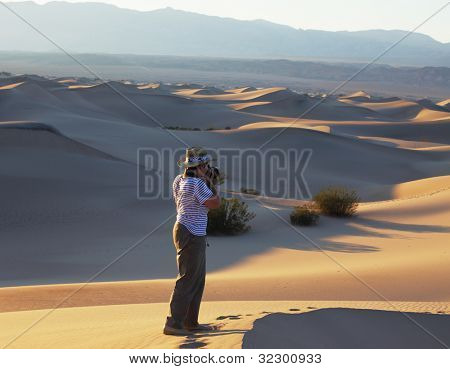 A magnificent sunrise amongst the sand dunes. Woman photographer in a striped T-short photographing sand waves