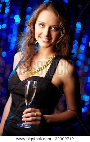 Tilt up of a girl dressed elegantly in black holding a flute with a drink and smiling at cam