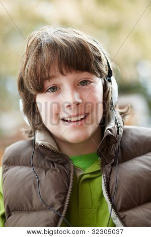 Boy Wearing Headphones And Listening To Music Wearing Winter Clothes