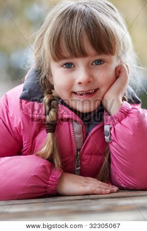 Outdoor Portrait Of Young Girl Wearing Winter Clothes