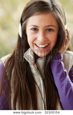 Teenage Girl Wearing Headphones And Listening To Music Wearing Winter Clothes