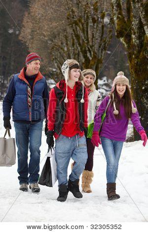 Família adolescente carregando compras caminhando ao longo da rua de Snowy