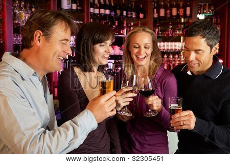 Group Of Friends Enjoying Drink Together In Bar
