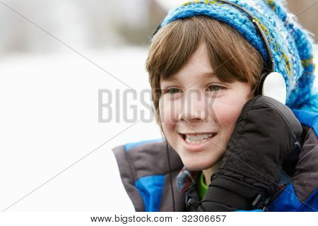 Boy Wearing Headphones And Listening To Music Wearing Winter Clothes In Snowy Landscape