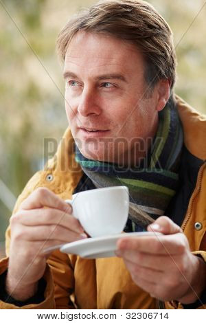 Man In Outdoor Caf���½ With Hot Drink  Wearing Winter Clothes