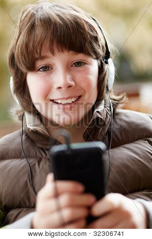 Boy Wearing Headphones And Listening To Music On Smartphone Wearing Winter Clothes