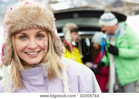 Mother Smiling At Camera Whilst Family Load Skis In Boot Of Car