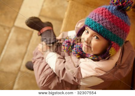Young Girl Sitting On Wooden Seat Putting On Warm Outdoor Clothes And Boots