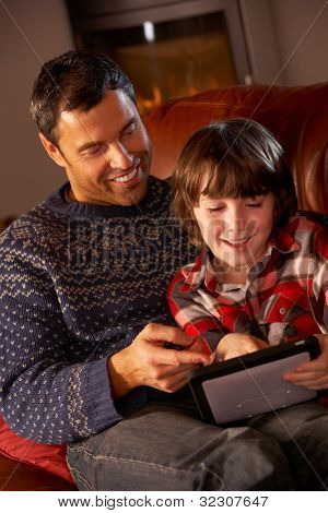 Father And Son Using Tablet Computer By Cosy Log Fire