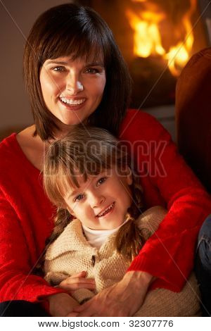 Mother And Daughter Relaxing On Sofa By Cosy Log Fire