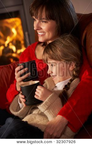 Mother And Daughter Relaxing With Hot Drink Watching TV By Cosy Log Fire