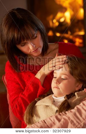 Mother Comforting Sick Daughter On Sofa By Cosy Log Fire