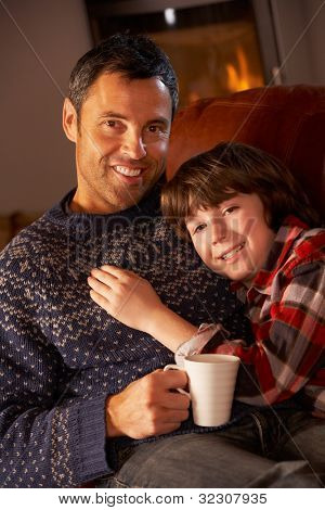 Father And Son Relaxing With Hot Drink Watching TV By Cosy Log Fire