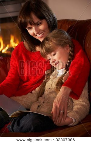 Mother And Daughter Sitting On Sofa And Reading Book By Cosy Log Fire