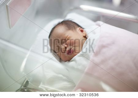 new born infant asleep in the blanket in delivery room