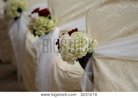 Floral Arrangements On Chairs At A Wedding