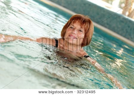 Mature lady swimming at swimming pool.