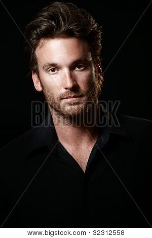 Portrait of handsome man wearing black shirt, black background, looking at camera.