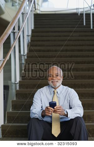 Senior African businessman using electronic organizer on stairs