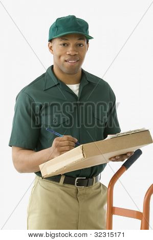 Studio shot of African delivery man with package and handtruck