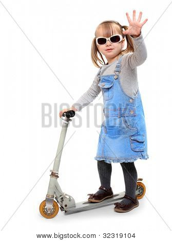 Little girl riding her children scooter.