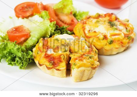 Mini quiche, vegetable pie served with tomato and lettuce salad