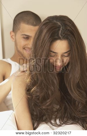 Hispanic man giving Hispanic woman a shoulder massage