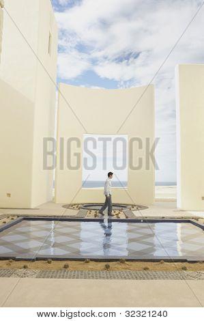 Man walking past luxury hotel pool