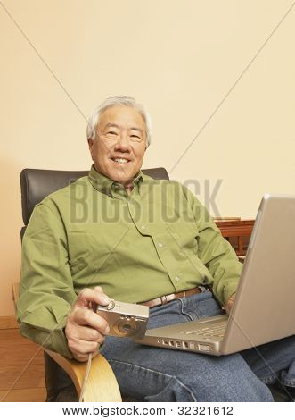 Senior Asian man with laptop and digital camera