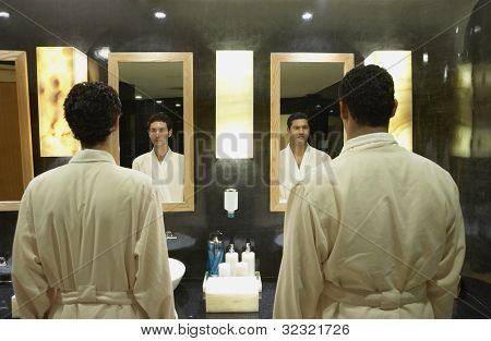 Two men in robes in front of bathroom mirrors