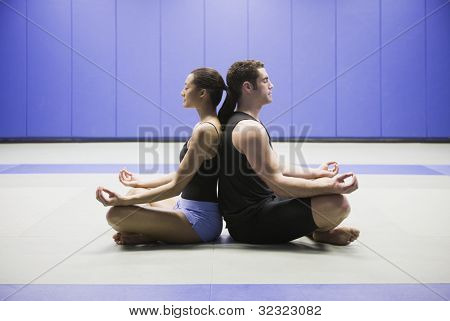 Man and woman meditating back to back