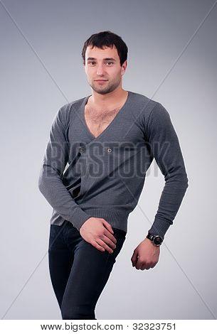 Moda homem musculoso em fundo cinza