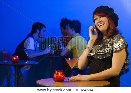 Woman with cocktail and cell phone standing at nightclub table
