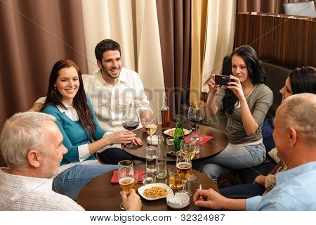 Business people having drink after work taking picture of themselves