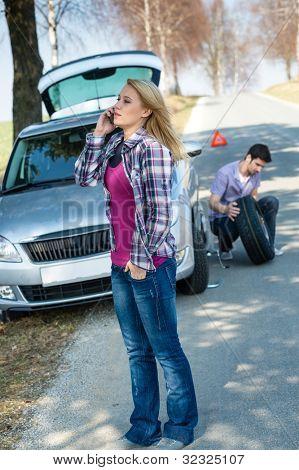 Car trouble woman calling road assistance man change broken wheel
