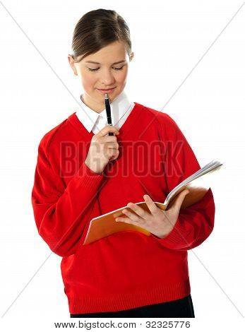 Cute School Girl Thinking And Looking Into Notebook