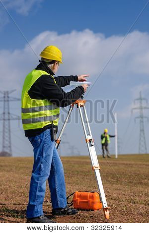 Land surveyors measuring with tacheometer point direction looking at plan