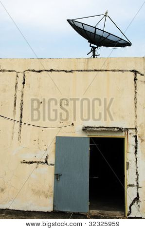 Black satellite dish and old door
