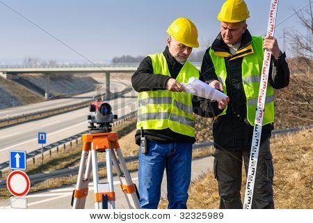 Land surveyors on highway reading geodesist plans use tacheometer