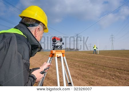 Land surveyors measuring with tacheometer speaking through transmitter