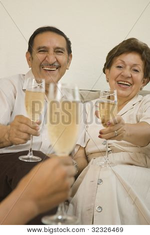 Senior Hispanic couple smiling and toasting with champagne
