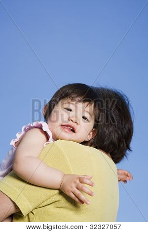Asian baby looking over mother's shoulder