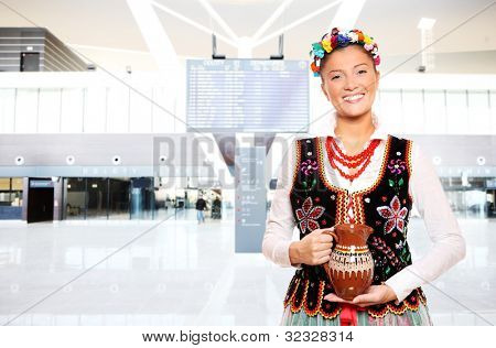 A portrait of a beautiful and hospitable Polish woman in a traditional outfit at the airport