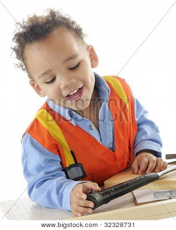 "Closeup view of a two-year-old ""construction worker"" happily at his tool bench.  On a white background."