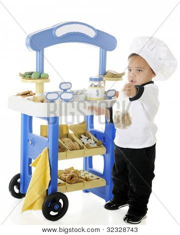 "A preschool ""chef"" handing a bag of cookies to a customer (unseen) in front of his bakery vending stand.  The stand's signs are left blank for your text.  On a white background."