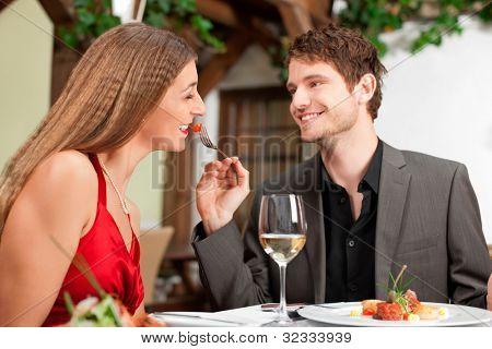 Feliz joven mujer de alimentación en la mesa del restaurante
