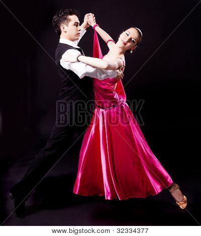 a couple dancing against black studio background