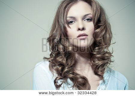 Closeup portrait of a sexy young woman with curly hair and perfect skin