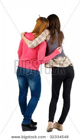 Back view of two young girl  pointing at wall . Rear view people collection.  backside view of person. beautiful woman friends  showing gesture. Rear view. Isolated over white background.