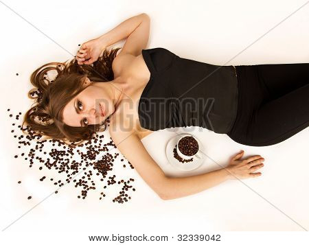 Beautiful Woman Lie On Coffee Beans With Coffee Cup